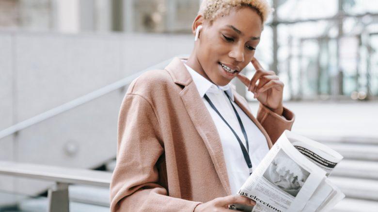 Black woman outside reading a newspaper
